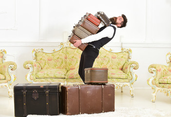 Man with beard and mustache wearing classic suit delivers luggage, luxury white interior background. Macho, elegant porter carries heavy pile of vintage suitcases. Butler and service concept.