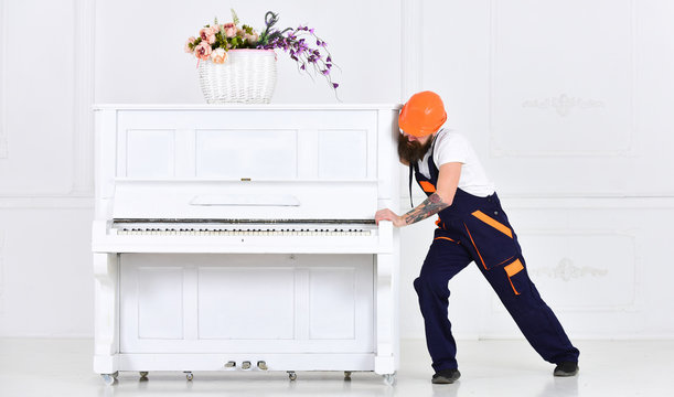 Man with beard worker in helmet and overalls pushes, efforts to move piano, white background. Loader moves piano instrument. Courier delivers furniture, move out, relocation. Heavy loads concept.