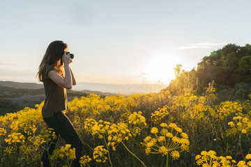 Woman taking pictures on mountain with yellow flowers