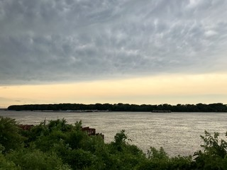 Sunset over Mississippi River with barges and tree line in the distance