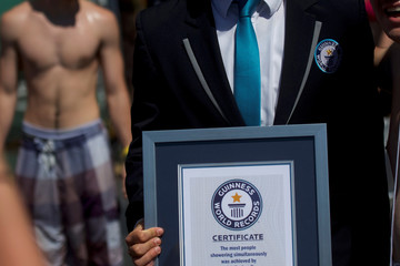 A Guinness World Records official holds a certificate for concert goers who set the record for the most people taking a simultaneous shower, during the second day of the Firefly Music Festival in Dover, Delaware