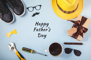 Father's day background or card Tools Yellow hat Glasses Sneakers Cup of coffee Cigar Gift on a blue background Text Flat lay Top view
