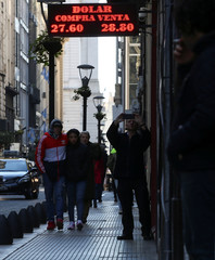 Pedestrians walk past an electronic board showing currency exchange rates in Buenos Aires' financial district