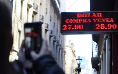 A pedestrian takes a picture of an electronic board showing currency exchange rates in Buenos Aires' financial district