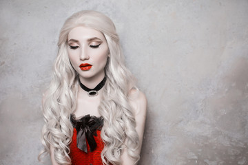Luxurious blonde woman with beautiful long white hair and red lips on a gray background.