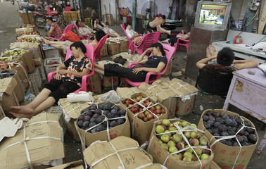 Vendors nap on chairs amongst boxes of fruits at a wholesale fruit and vegetable market in Wuhan