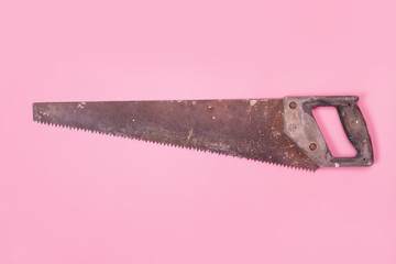The old saw lies on a pink background. Tools for repair