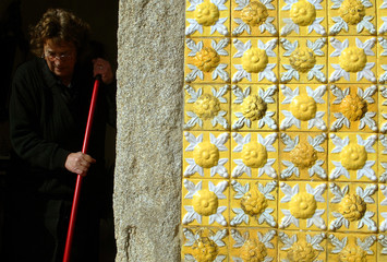 OLD WOMAN CLEANS THE ENTRANCE OF HER HOME IN PORTO.