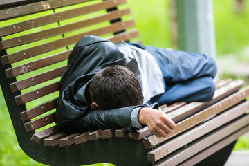 man is sleeping on a park bench