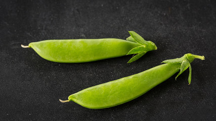 Freshly picked snow peas on a black background.