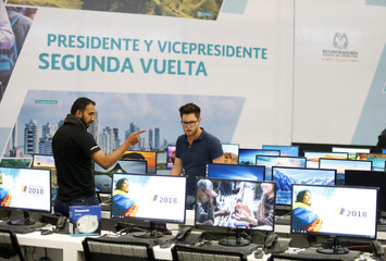Two workers are finishing up the final details for the second round of the presidential election in Bogota