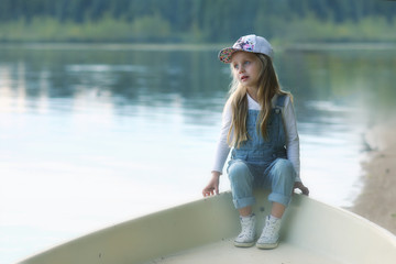 Thoughtful cute little girl in a boat on the lake in the early morning