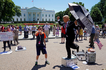 A boy dances along with a street performer dressed as U.S. President Donald Trump in front of the White House in Washington