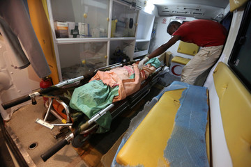 Medic places woman's body in ambulance after she was killed by clashes between government forces and Houthi fighters near Hodeidah