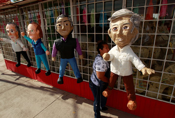 A woman hangs up pinatas for sale depicting Mexican presidential candidates outside a pinata store in Ciudad Juarez