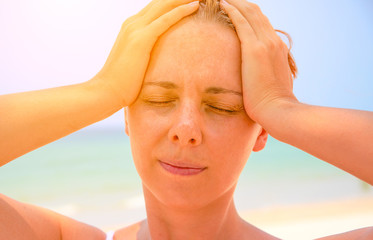 Young woman suffering with headache. Woman on hot beach with sunstroke. Health problem on holiday.