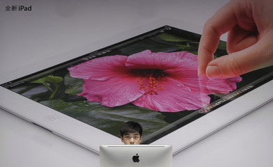 An employee sits in front of a poster advertising the New iPad at an Apple dealership in Wuhan