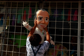 A woman hangs up a a pinata for sale depicting Mexican presidential candidate Jose Antonio Meade of the Institutional Revolutionary Party (PRI), outside a pinata store in Ciudad Juarez