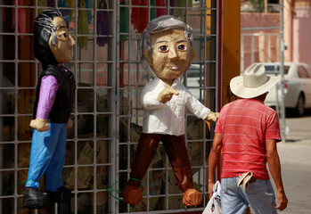 A man walks past pinatas for sale depicting Mexican presidential candidates outside a pinata store in Ciudad Juarez