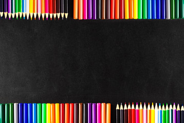Back to school background with a lot of colorful felt-tip pens and colorful pencils on the black scratched chalkboard