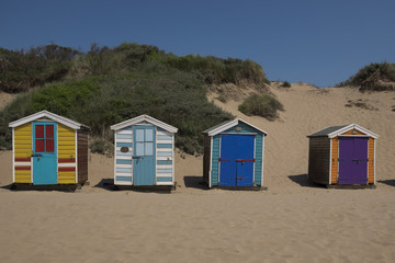 Brightly painted beach huts in a row on Saunton Sands, North Devon UK. backdrop of sand dunes and blue sky on a sunny summers day