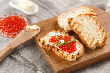 toasts with butter and Red caviar on a wooden cutting Board