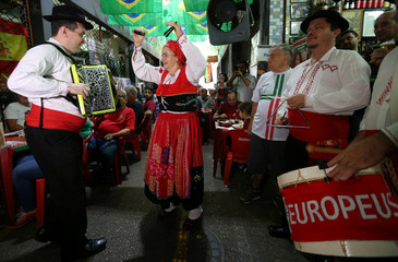 Portuguese fan dance before the start of World Cup soccer match between Spain and Portugal at the Municipal Market of foods in Rio de Janeiro