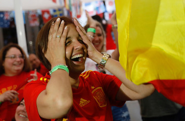 Spanish soccer fans react during the World Cup 2018 match between Spain and Portugal in a bar in Madrid