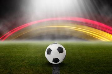 Fußball im Stadion vor Lichteffekten in Deutschland Farben