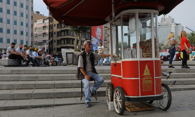 A street vendor waits for customers as an election poster for Turkey's President Tayyip Erdogan is seen on the background in Istanbul,
