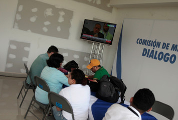 Journalists follow a live transmission of talks between representatives of Nicaragua's government and local civic groups, mediated by Catholic Church leaders, in Managua