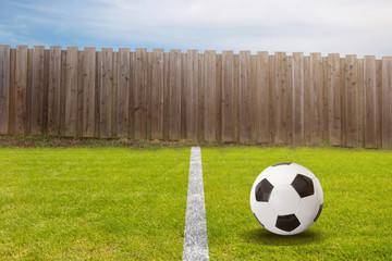 Fußball auf dem Spielfeld vor dem Gartenzaun vom Nachbarn