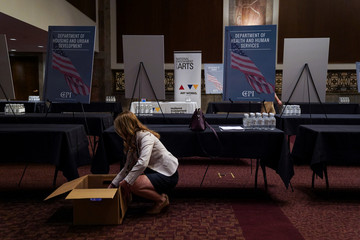A woman prepares a stand at the Executive Branch Job Fair hosted by the Conservative Partnership Institute at the Dirksen Senate Office Building in Washington