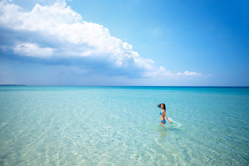 Beautiful happy woman standing in swimsuit in azure sea, vacation concept