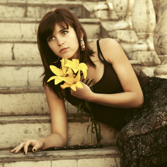 Sad young woman with a flowers sitting on steps