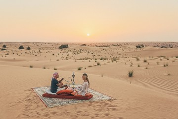 Canvas Prints Abu Dhabi Romantic couple seating on a carpet in the Emirates desert