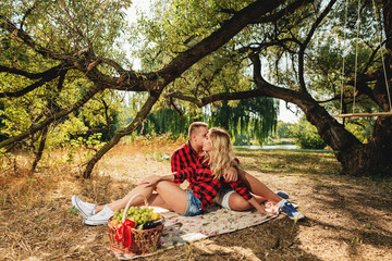 Picnic time. Young couple having fun on picnic in the park. Love and tenderness, dating, romance, lifestyle concept