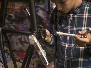 close up mechanic with instrument tools fixing the bmx bicycle