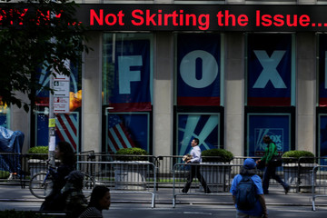 People pass by ads of Fox News channel at the News Corporation building in the Manhattan borough of New York City, New York