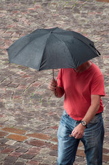 portrait of man with umbrella on cobbles place  in the city