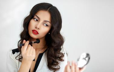 Beautiful girl with perfect skin applying makeup.