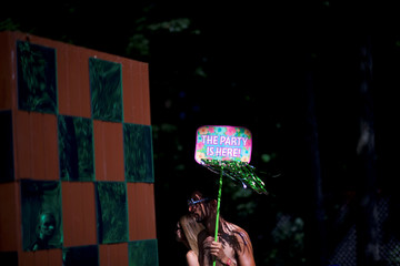 "A reveler holds a placard stating ""THE PARTY IS HERE!"" on the second day of the Firefly Music Festival in Dover, Delaware U.S."