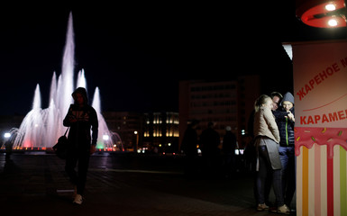 People use their mobiles at a square in downtown of Saransk, Russia