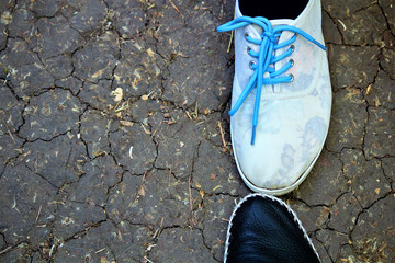 Top view of two legs in flat leather shoes and sports shoes. Against the background of dry and cracked earth. The concept of arid climate, drought. Selective focus, copy space, top view