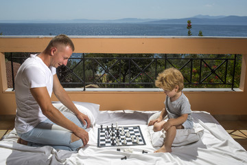 Smart toddler concept Dad with child play intellectual game Father and little son play chess on balcony nature and sea on background