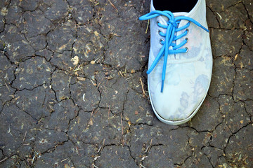 Top view of one foot in athletic shoes. Against the background of dry and cracked earth. The concept of arid climate, drought. Selective focus, copy space, top view