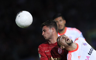 Bayern Munich's Ribery jumps for ball with Regensburg's Djuricin during their German DFB Cup soccer match in Regensburg