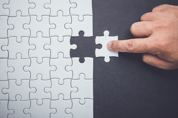Hand holding pieces of jigsaw puzzle and insert into the missing hole