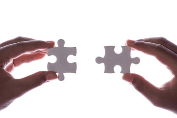 Connection concept : Hands holding pieces of jigsaw puzzle on white