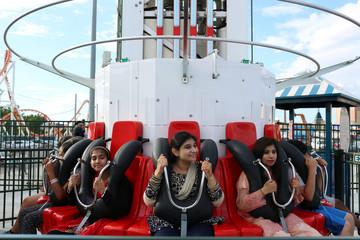 Pakistani American girls celebrate Eid Al-Fitr at Luna Park in Coney Island, Brooklyn, New York